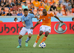 July 18, 2018 - Houston, TX, U.S. - HOUSTON, TX - JULY 18:  Houston Dynamo midfielder Oscar Garcia (27) keeps the ball away from Sporting Kansas City midfielder Roger Espinoza (17) during the US Open Cup Quarterfinal soccer match between Sporting KC and Houston Dynamo on July 18, 2018 at BBVA Compass Stadium in Houston, Texas. (Photo by Leslie Plaza Johnson/Icon Sportswire) (Credit Image: © Leslie Plaza Johnson/Icon SMI via ZUMA Press)