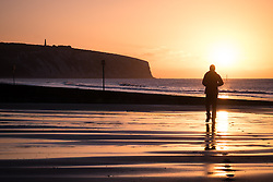 © Licensed to London News Pictures. 07/04/2016. Sandown, UK. A man walking along the beach during sunrise at Sandown Bay on the Isle of Wight this morning, Thursday 7th April 2016. Photo credit : Rob Arnold/LNP