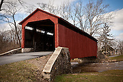 Amish women rides her bike through Pool Forge Covered Bridge Caenarvon Township, PA