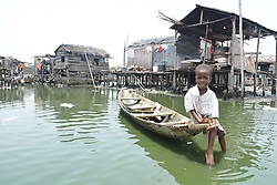 LAGOS, NIGERIA - MARCH 24: Nigerian kid sits over a boat as Police officers demolish unlicensed constructions which were built over lake at the Otodo Gbame slum neighnoorhood in Lagos, Nigeria on March 24, 2017.<br /> <br />  Ndubuisi Emmanuel  (Credit Image: RealTime Images)