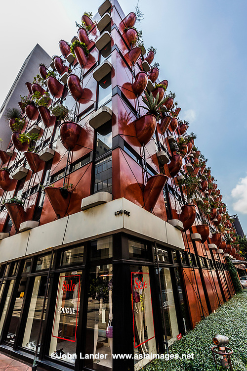 Organic Building Osaka -  Space is limited in Japan so there is not much extra room for garden space.  One solution to this is the concept of a vertical garden, sometimes known of as green walls or living walls, The Organic Building in Osaka is a vertical garden borrowing motifs from natural bamboo.  Bamboo was chosen because of its inherent undulating qualitiy and verticality, and strength.  The exterior is covered with red panels with fiberglass planters protruding from the building containing more than eighty types of plants.  The plants are watered by built in pipes that are computer controlled.