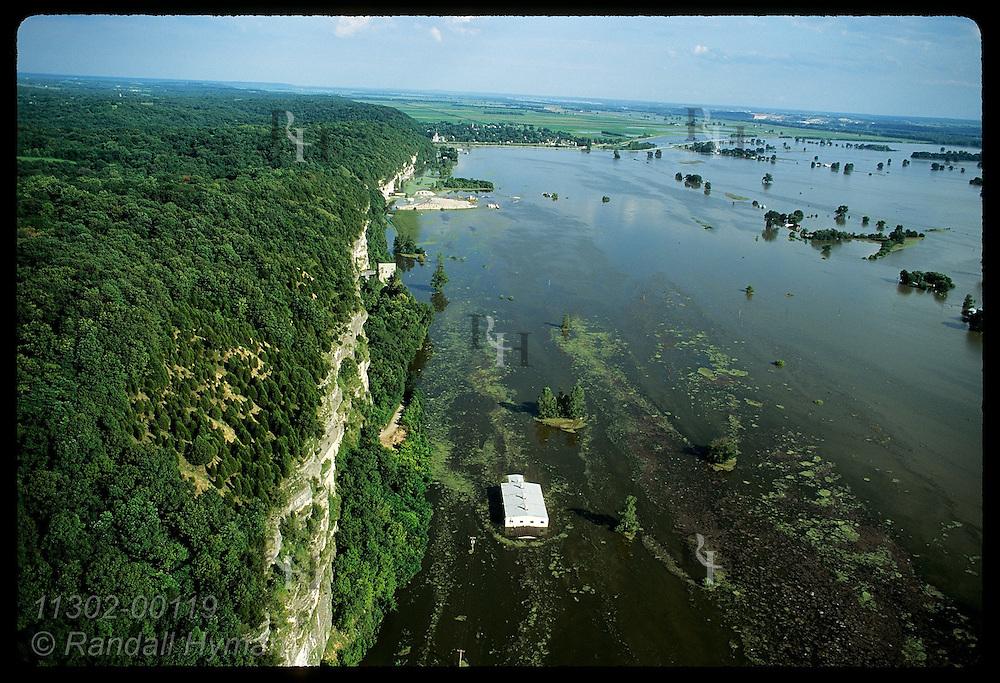 Aerial: Mississippi floods a bldg along base of bluffs outside of levee on 8/3/93;Prairie du Rochr Illinois