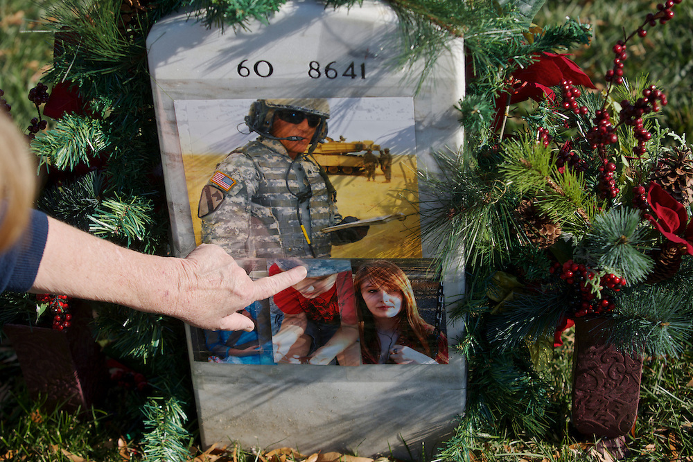ARLINGTON - NOVEMBER 11: Linda Lamie, of Georgia, points to the grave of her son, Sgt. Gene L. Lamie, on Veteran's Day at Arlington National Cemetery on November 11, 2012 in Arlington, Virginia. Sgt. Lamie was killed during Operation Iraqi Freedom in 2007 at the age of 25.