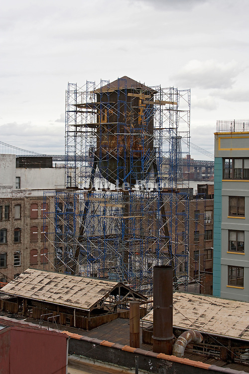 old rusty watertower in  scaffolding on top of an industrial building in Brooklyn New York City