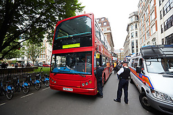 © Licensed to London News Pictures.  11/06/2013. LONDON, UK. A red London bus wais to transport arrested anti G8 protesters in Golden Square, London.  Photo credit: Cliff Hide/LNP