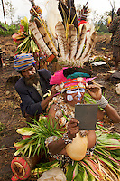 Members of a Western Highlands Province group prepare to perform in the cultural show.  They are wearing Bird of Paradise and other plumes in their headdresses.  Mount Hagen, Paua New Guinea.