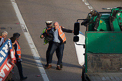 Ockham, UK. 21st September, 2021. A Surrey Police officer restrains an Insulate Britain climate activist who walked into the clockwise carriageway of the M25 between Junctions 9 and 10 as part of a campaign intended to push the UK government to make significant legislative change to start lowering emissions. Both carriageways were briefly blocked before being cleared by Surrey Police. The activists are demanding that the government immediately promises both to fully fund and ensure the insulation of all social housing in Britain by 2025 and to produce within four months a legally binding national plan to fully fund and ensure the full low-energy and low-carbon whole-house retrofit, with no externalised costs, of all homes in Britain by 2030.