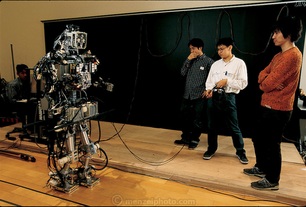 At a robotics exhibition in Tokyo, Japan,  Samuel Setiawan (in white shirt) and two other Waseda University graduate students cautiously stand by during a lengthy prewalk checklist for WABIAN-RII. To their dismay, the robot initially has trouble negotiating the wooden floor, which is much springier than the concrete floor in the lab, where it had been programmed to walk. After some frantic reprogramming, Setiawan, the primary student researcher on the project, is able to make WABIAN walk its assigned path. From the book Robo sapiens: Evolution of a New Species, page 38.