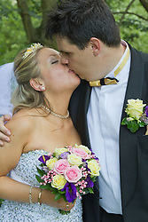Visually impaired bride and groom kissing.