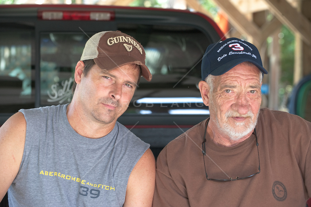 Two men with attitude sitting on the back of a truck