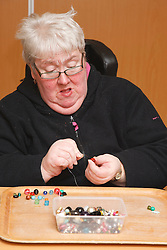 Client doing craft activity at a resource for people with physical and sensory impairment.