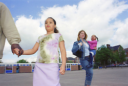 Single parents walking across primary school playground with young children,