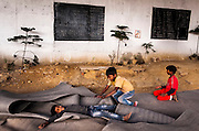 18th March 2014, Shakarpur, New Delhi, India. Children play on the foam mats before the teachers arrive at a makeshift school under a metro bridge near the Yamuna Bank Metro station in Shakarpur, New Delhi, India on the 18th March 2014<br /> <br /> Rajesh Kumar Sharma (born 01/02/1970), started this makeshift school in 2011. Six mornings a week he teaches underprivileged children for three hours while his younger brother replaces him at his general store in Shakarpur. His students are children of labourers, rickshaw-pullers and farm workers. This is the 3rd site he has used to teach under privileged children in the city, he began in 1997. <br /> <br /> PHOTOGRAPH BY AND COPYRIGHT OF SIMON DE TREY-WHITE<br /> + 91 98103 99809<br /> email: simon@simondetreywhite.com<br /> photographer in delhi<br /> journalist