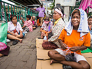 """07 AUGUST 2014 - BANGKOK, THAILAND: People wait for food distribution to start at Pek Leng Keng Mangkorn Khiew Shrine. Thousands of people lined up for food distribution at the Pek Leng Keng Mangkorn Khiew Shrine in the Khlong Toei section of Bangkok Thursday. Khlong Toei is one of the poorest sections of Bangkok. The seventh month of the Chinese Lunar calendar is called """"Ghost Month"""" during which ghosts and spirits, including those of the deceased ancestors, come out from the lower realm. It is common for Chinese people to make merit during the month by burning """"hell money"""" and presenting food to the ghosts. At Chinese temples in Thailand, it is also customary to give food to the poorer people in the community.     PHOTO BY JACK KURTZ"""