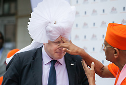 'Boris Johnson visits Hindu Temple. The Mayor of London Boris Johnson gets a 'Bindi' by the spiritual leader Acharya Swamishree   after being dressed with a 'Pagh' (type of Turban) during a visit to the Shree Swaminarayan Mandir, a major new Hindu temple being built in Kingsbury. Shree Swaminarayan Mandir, London, United Kingdom. Wednesday, 28th May 2014. Picture by Daniel Leal-Olivas / i-Images