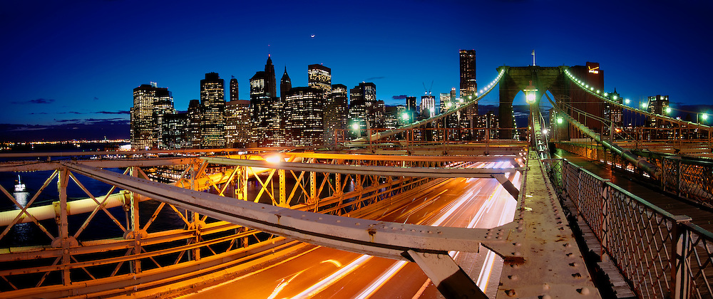 Panorama of Brooklyn bridge busy traffic at night and Manhattan skyline with skyscrapers