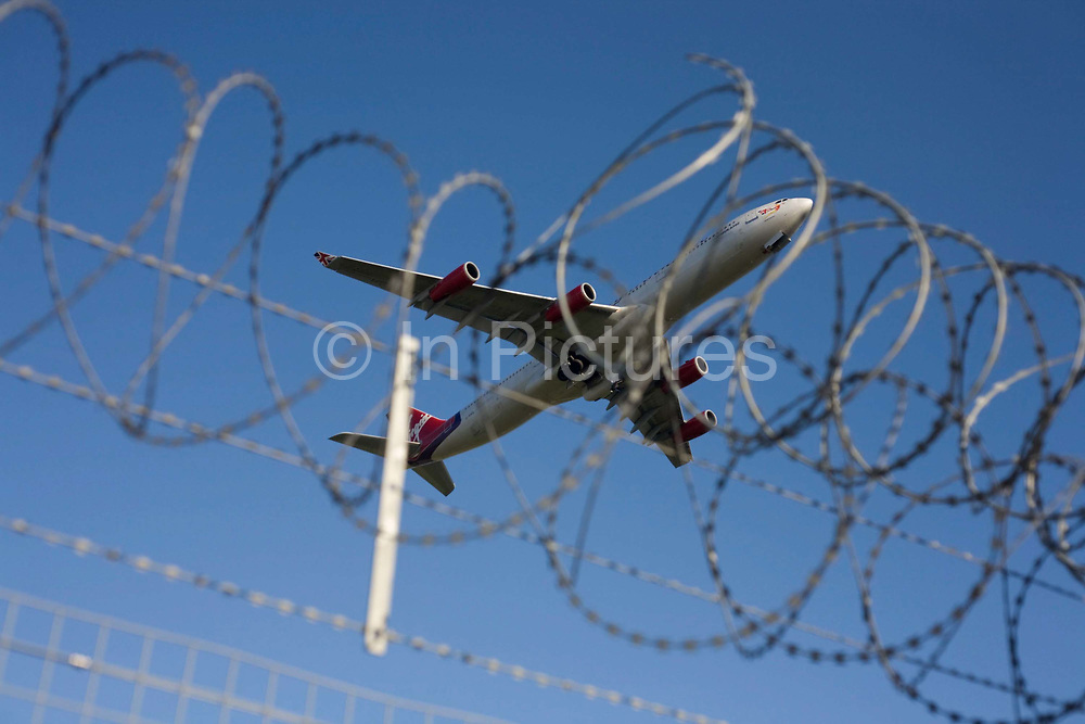 """A Virgin Atlantic Airbus A340 crosses the perimeter fence at Heathrow Airport on its way to an international destination. Seen from below, the passing Jumbo takes-off and climbs under full take-off power over the surrounding airfield security fence. Its razor-wire is an effective deterrent against protesters or terrorists and symbolises the lengths that airport authorities (in this case BAA) need go to to ensure their property is safe. The aircraft is seen almost entangled in the secure wire as if passing through the mesh. From writer Alain de Botton's book project """"A Week at the Airport: A Heathrow Diary"""" (2009)."""