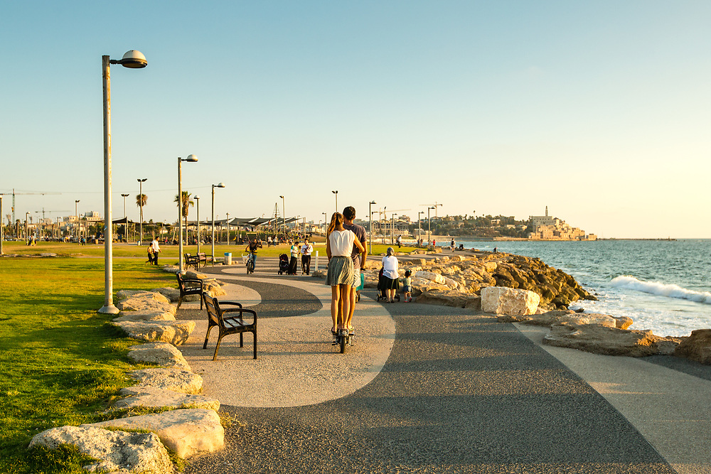 The Old City of Jaffa and the Mediterranean Sea provide the backdrop, as a couple is seen riding an electric scooter at the promenade of Charles Clore Park, in Tel Aviv's Neve Tzedek neighborhood