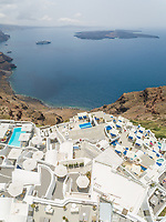 Aerial view over traditional white houses with large cruiser at sea, Santorini island, Greece.