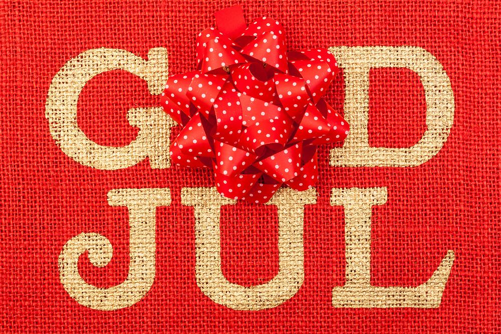 «God jul»-tekst silketrykket på rød striesekk, med gaverosett over O-en.