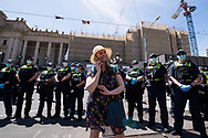 A woman protesting the state government's lockdown talks on her phone in front of a police line. The groups who have organised the many Freedom Day protest over the last 3 months, attempted to march to State Parliament on Melbourne Cup Day demanding the sacking of Premier Daniel Andrews for the lockdown and attacks on their civil liberties, where they were met with a heavy police presence.  (Photo by Michael Currie/Speed Media)