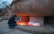 "Christian Y. Schmidt  lights a candle at a makeshift memorial at  Arnswalder Platz in Berlin, Germany, January 17,  2021. The memorial is part of the initiative  ""Corona-Tote sichtbar machen"" (lit. Make corona deaths visible) by Christian Y. Schmidt and Veronika Radulovic,  since December 6, 2020, people gather at the fountain of Arnswalder Platz every Sunday at 16:00, light candles and place placards with the current death toll reported in Germany at the time. The death toll in Germany by variouse sources revolved around 47,000."