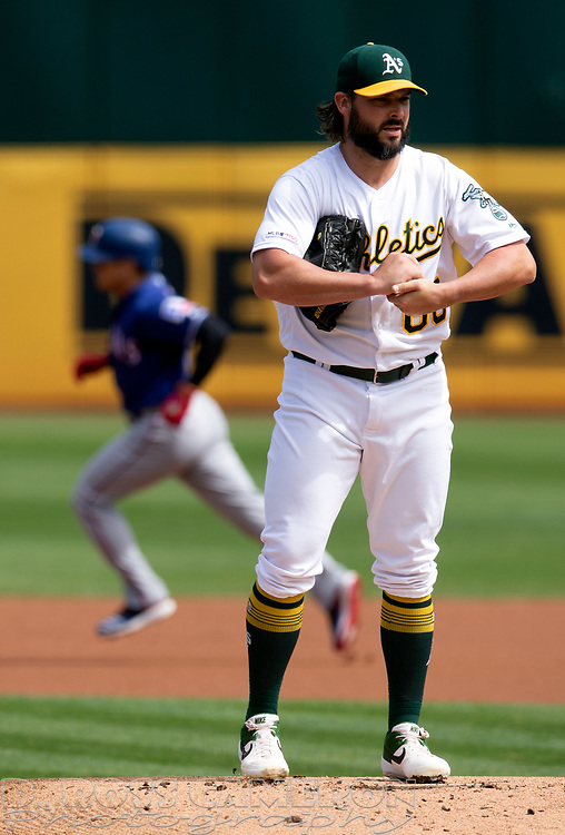 Oakland Athletics starting pitcher Tanner Roark (60) rubs up a new baseball while he waits for Texas Rangers designated hitter Shin-Soo Choo to run out his leadoff home run during the first inning of a baseball game, Sunday, Sept. 22, 2019, in Oakland, Calif. (AP Photo/D. Ross Cameron)