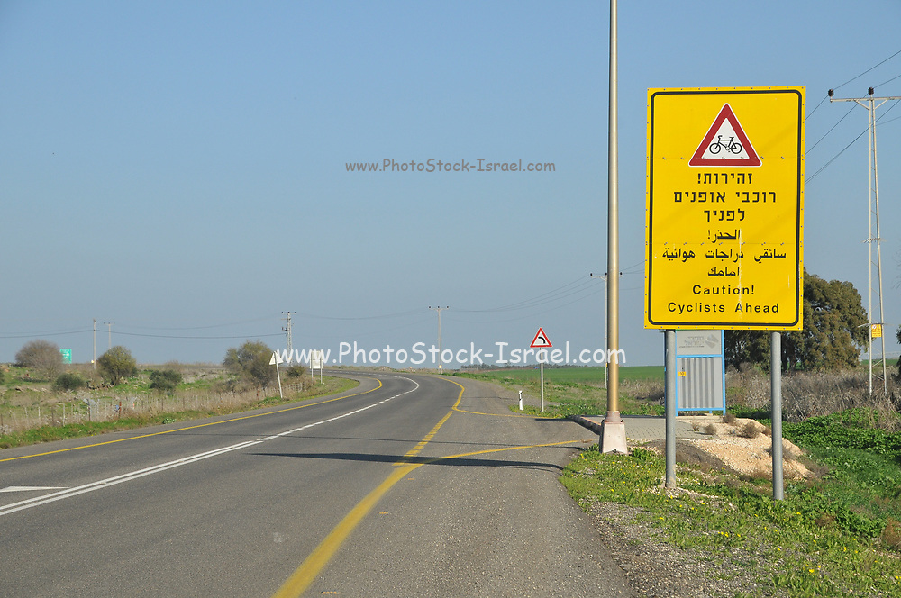 Caution cyclists ahead yellow warning sign in Hebrew, Arabic and English. Photographed in the Golan Heights, Israel