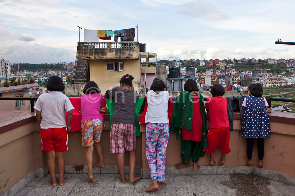 Seven Nepalese girls watching a neighbor from the balcony of their care home in Kathmandu, Nepal.  They are all orphans who have been rescued by Friends of Needy Children organization. It provides a loving home for boys and girls who are orphaned or abandoned.  Abject poverty, domestic violence and armed conflict have caused many Nepalese children orphaned and homeless.