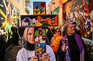 Adrienne Plasse of the St. John of God Church carries a cross through Clarion Alley during an Ash Wednesday procession with several faith leaders in San Francisco, Calif., March 1, 2017. Plasse has maintained her church with sanctuary status for undocumented immigrants for over 30 years.