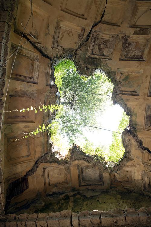 hole in old dilapidated elegant ceiling