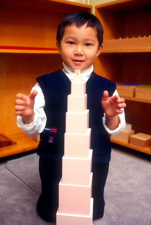 Small boy building the Montessori tower with pink blocks,