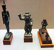 Egyptian bronze sculpture of the Gods including Bess (centre), Amun (Left) and Imhotep (the architect ) kneeling, (Right). From the Ptolemaic period in Egypt, 332 BC -30 AD.