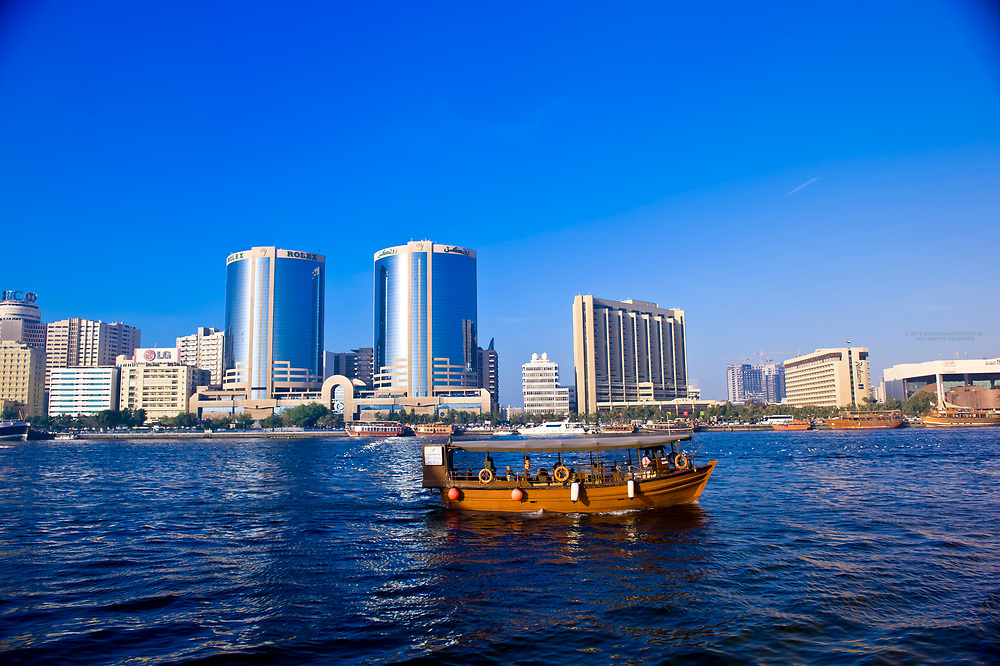Dows and abras (traditional boats) on Dubai Creek with the Deira section behind, Dubai, United Arab Emirates