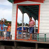 South America, Brazil, Amazon. A mother watches as her tow boys wave to passing boats on the Amazon.