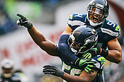 Seahawks linebacker Bobby Wagner (54) jumps on defensive end Cliff Avril (56) as Avril celebrated a third quarter sack of Green Bay quarterback Aaron Rodgers, during their game January 18, 2015.  The Seahawks won 28-22.