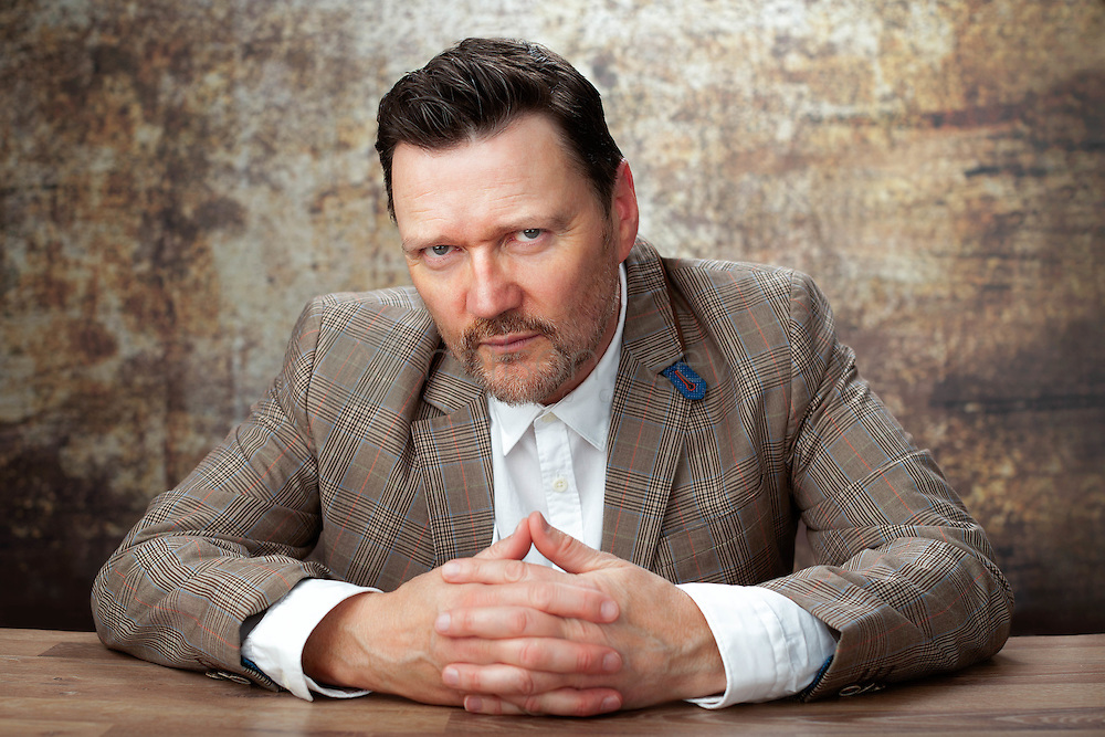 In this portrait of Ian Puleston-Davies the photographer with hands crossed on the table in front of him.