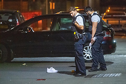 © Licensed to London News Pictures. 20/07/2020. London, UK. Two police officers look over the crime scene where a show sits next to a car in Bethnal Green. An investigation has been launched after a person was rammed by a car in Bethnal Green, the person was rammed by the vehicle into a fence. Photo credit: Peter Manning/LNP