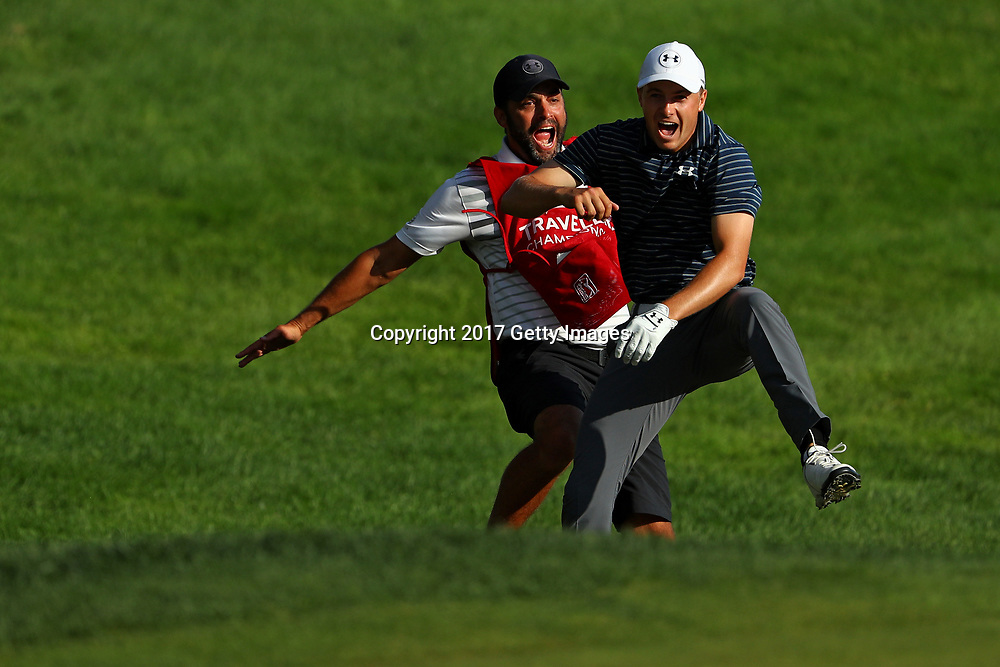 Jordan Spieth of the United States celebrates with caddie Michael Greller after chipping in for birdie from a bunker on the 18th green to win the Travelers Championship in a playoff against Daniel Berger of the United States (not pictured) at TPC River Highlands on June 25, 2017 in Cromwell, Connecticut.