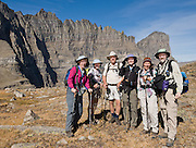 """A hiking group enjoys Piegan Pass and Mount Gould (far right), in Glacier National Park, Montana, USA. A scenic walking traverse starts from Siyeh Bend over Piegan Pass to Many Glacier, visiting glorious mountains, valleys and lakes over 13 miles (2260 feet up, 3520 feet down). Since 1932, Canada and USA have shared Waterton-Glacier International Peace Park, which UNESCO declared a World Heritage Site (1995) containing two Biosphere Reserves (1976). Rocks in the park are primarily sedimentary layers deposited in shallow seas over 1.6 billion to 800 million years ago. During the tectonic formation of the Rocky Mountains 170 million years ago, the Lewis Overthrust displaced these old rocks over newer Cretaceous age rocks. Glaciers carved spectacular U-shaped valleys and pyramidal peaks as recently as the Last Glacial Maximum (the last """"Ice Age"""" 25,000 to 13,000 years ago). Of the 150 glaciers existing in the mid 1800s, only 25 active glaciers remain in the park as of 2010, and all may disappear by 2020, say climate scientists. For licensing options, please inquire."""