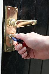 Young woman locking her flat door,