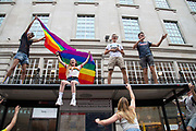 Party goers watch the parade from the top of a bus stop as members of the Lesbian, Gay, Bisexual and Transgender (LGBT) community take part in the annual Pride Parade on 6th July, 2019 in London,United Kingdom. (photo by Claire Doherty/In Pictures via Getty Images)
