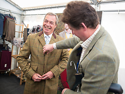 © Licensed to London News Pictures. 31/07/2015. Leeds , UK . NIGEL FARAGE tries on a jacket at the Ratcatcher marquee with Charles Wall , at the CLA GameFair ( Country Landowners Association ) at Harewood House in Yorkshire . Photo credit: Joel Goodman/LNP