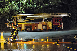 © Licensed to London News Pictures . 21/08/2013 . Stockport , UK . Firefighters tackle a large blaze at the J25 Recycling Centre in Bredbury , Stockport this morning (Wednesday 21st August 2013) where a building and bales of recyclable material are alight . The fire , which started late last night (20th August) is being tackled by more than 50 fire crew . The site , which is adjacent to a branch of Morrisons Supermarket and McDonalds , is off Junction 25 of the M60 motorway , exits for which are closed in both directions . Photo credit : Joel Goodman/LNP