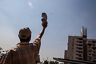A Morsi supporter holds his shoe at a military helicopter as it flies overhead.
