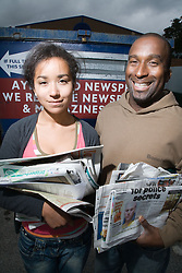 Father and daughter recycling old newspapers at the recycling bank,