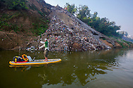 Jeremiah Kent paddles past a heaping mound of trash outside Mizapur, India. This was Day 4 of a week long standup paddle mission down the Ganges River.