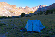 Sunrise over a tent in the valley near Alger Lakes, with a view of Koip Peak in the background; Ansel Adams Wilderness, Inyo National Forest, Sierra Nevada Mountains, California, USA.