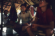 1989: Semi-nomadic Penan native, Banai Tebai, smokes a cigarette inside a 'sulap' settlement made from bamboo, wood and rattan. Long Tedang, Limbang district, Sarawak, Borneo<br /> <br /> Tropical rainforest and one of the world's richest, oldest eco-systems, flora and fauna, under threat from development, logging and deforestation. Home to indigenous Dayak native tribal peoples, farming by slash and burn cultivation, fishing and hunting wild boar. Home to the Penan, traditional nomadic hunter-gatherers, of whom only one thousand survive, eating roots, and hunting wild animals with blowpipes. Animists, Christians, they still practice traditional medicine from herbs and plants. Native people have mounted protests and blockades against logging concessions, many have been arrested and imprisoned.