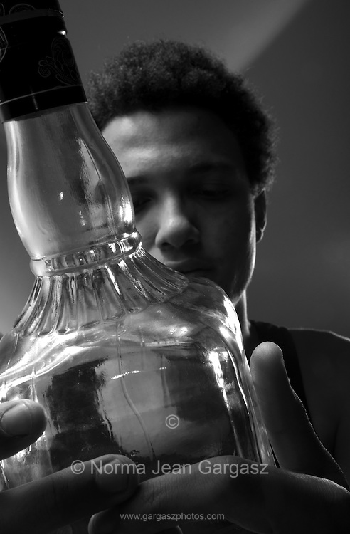 A young man with a bottle of liquor.